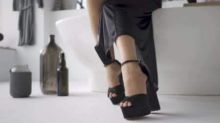 talons : Close-up of female feet in elegant black clothes sitting on teh bath in the bathroom. Bottles standing on the floor. The girl preparing for the date. Happy mood