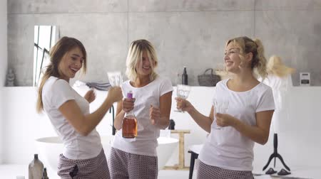 pletyka : Three joy girlfriends in white t-shirts spending time together at home drinking alcohol. Women celebrating, raising hands up. Hen-party, pajama party. Girls have fun indoors