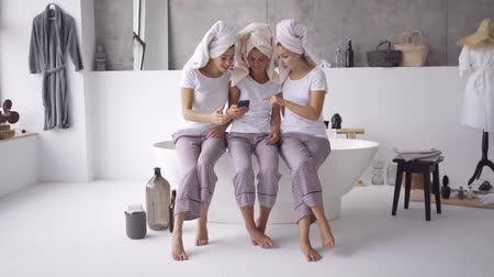 pata de pollo : Three positive girlfriends in the same pajamas and towels on heads spending time together at home looking on the cellphone in the bathroom. Hen-party, pajama party. Girls have fun indoors