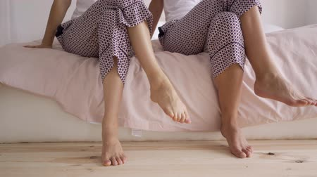 uguale : Close-up of female legs in the same pants putting one leg on another while sitting on the bed. Leisure indoors. Hen-party