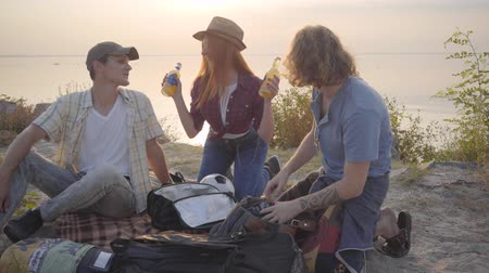 взял : Group of young friends making picnic with guitar and young girl took out of the bag cold beer or lemonade