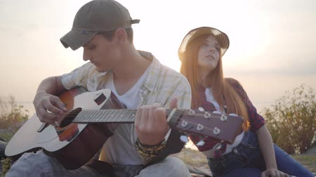 biust : Hipster young guy playing guitar and his girlfriend listening with interest on the background of evening summer beach Wideo