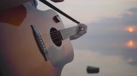 бюст : Hipster young guy playing guitar and singing on the background of evening colorful sunset near summer beach. Close up