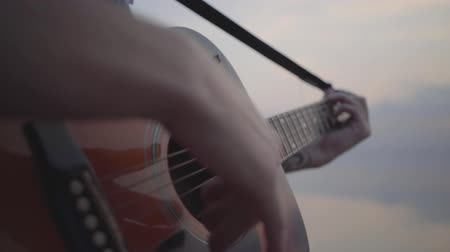 biust : Closeup of male hand playing guitar on the background of evening colorful sunset near summer beach. Wideo