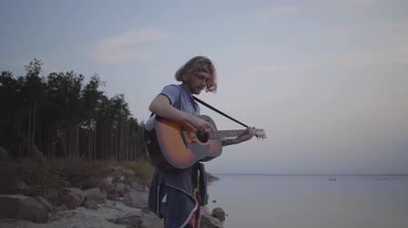 бюст : Hipster young guy playing acoustic guitar on the background of evening colorful sunset near summer beach.