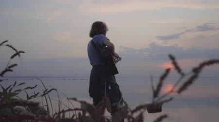 бюст : Young guy playing acoustic guitar on the background of evening colorful sunset near summer beach.
