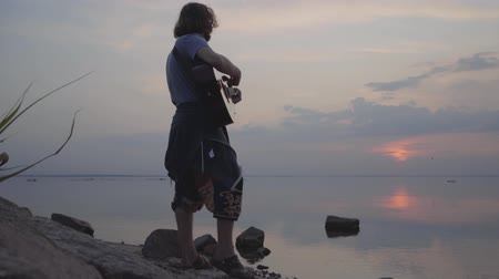 biust : Hipster young man playing acoustic guitar on the background of evening colorful sunset near summer beach.