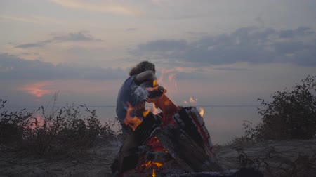 biust : Hipster man playing acoustic guitar on the background of evening colorful sunset and summer beach near bonfire