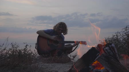 biust : Hipster young guy playing acoustic guitar on the background of evening colorful sunset and summer beach near bonfire