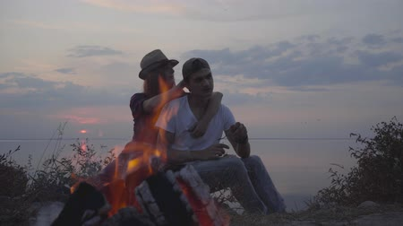 busto : Young couple hugging while sitting on the background of evening colorful sunset and summer beach near bonfire. Archivo de Video