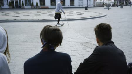 ösztönző : Young man with one leg on crutches training with skateboard in the background while people looking at him in the foreground. Disabled person rides on a skateboard. Motivation, active lifestyle