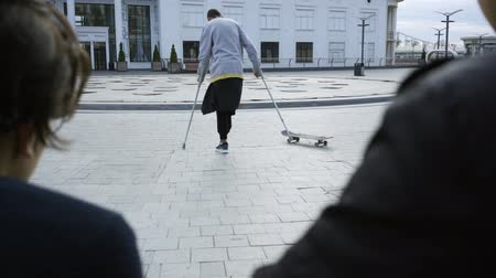 ösztönző : Man with one leg on crutches training with skateboard in the background while people looking at him in the foreground. Disabled person rides on a skateboard. Motivation, active lifestyle