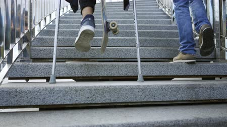 ösztönző : Young man with one leg on crutches with skateboard climbs the stairs faster than his friend. Active life of disabled person. The guy without leg enjoying his life. Motivation, never give up Stock mozgókép