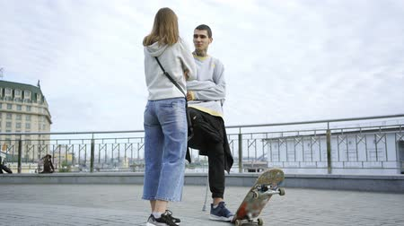 ösztönző : Young man with one leg on crutches with skateboard talking with his girlfriend on the street. Active life of disabled person. The guy without leg enjoying his life. Motivation, never give up