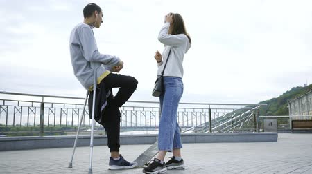 ösztönző : Handsome man with one leg on crutches with skateboard talking with his girlfriend on the street. Active life of disabled person. The guy without leg enjoying his life. Motivation, never give up