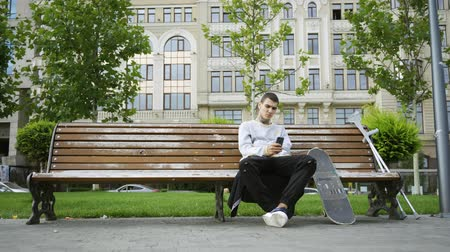 ösztönző : Attractive man sitting on the bench in the park listening to music on his cellphone. Crutches and skateboard are nearby. Active life of disabled person. Motivation, normal life, never give up Stock mozgókép