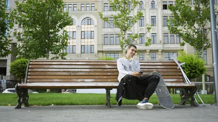 ösztönző : Young man sitting on the bench in the park listening to music on his cellphone. Crutches and skateboard are nearby. Active life of disabled person. Motivation, normal life, never give up