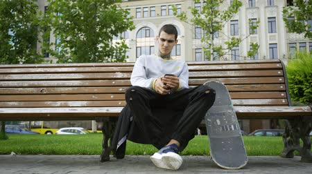 ösztönző : Handsome guy sitting on the bench in the park listening to music on his cellphone. Crutches and skateboard are nearby. Active life of disabled person. Motivation, normal life, never give up