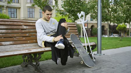hayran olmak : Handsome guy sits on the bench in the park listening to music on his cellphone. Crutches and skateboard are nearby. Active life of disabled person. Motivation, normal life, never give up