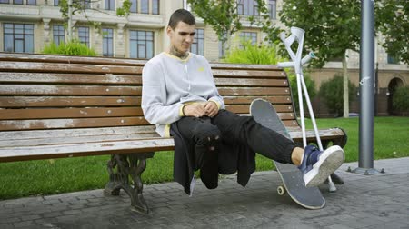ösztönző : Young man sitting on the bench in the park while listening to music on his cellphone then taking crutches and skateboard and riding away. Active life of disabled person. Motivation, normal life Stock mozgókép