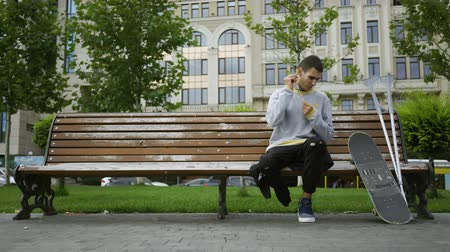 ösztönző : Attractive young man sitting on the bench in the park listening to music on his cellphone then taking crutches and skateboard and riding away. Active life of disabled person. Motivation, normal life