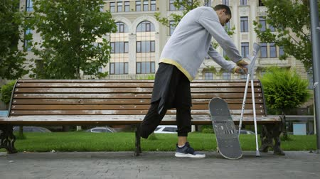 ösztönző : Attractive man sits on the bench in the park putting his crutches and skateboard nearby. Active life of disabled person. Motivation, normal life, never give up