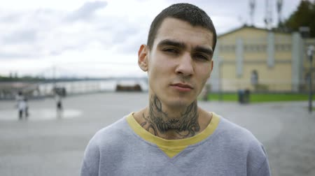 ösztönző : Portrait of a confident young man with a tattoo on his neck standing against the sky with clouds. The guy looking at the camera. Stock mozgókép