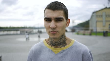 ösztönző : Portrait of a young man with a tattoo on his neck standing against the sky with clouds. The guy looking at the camera.