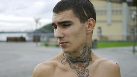 ösztönző : Portrait young man with a tattoo on his neck standing against the sky with clouds. The guy looking at the camera.