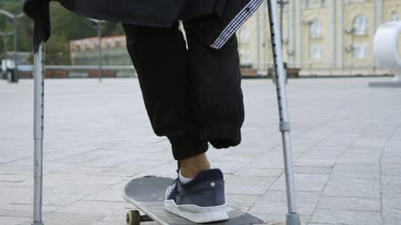 ösztönző : Unrecognized man with one leg on crutches riding on skateboard outdoors. Active life of disabled person. The guy without leg enjoying his life. Motivation, never give up. Slow motion. Stock mozgókép