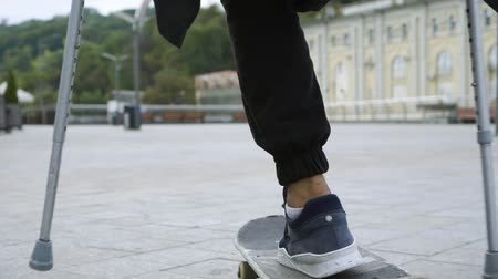 ösztönző : Close-up of man with one leg on crutches training and making tricks. Disabled person rides on a skateboard. Motivation, active lifestyle, never give up. Slow motion
