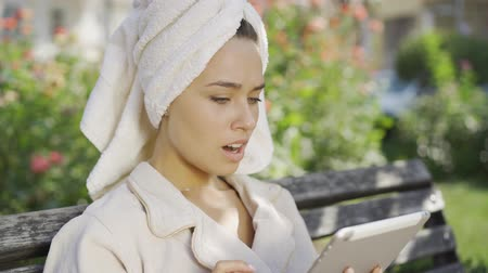 towel white : Portrait of adorable young woman in bathrobe with towel on head sitting on the bench in the park checking information on tablet. Confident girl enjoying sunny day outdoors