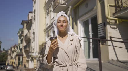 甘さ : Portrait cute smiling young woman in bathrobe with towel on head walking down the street drinking coffee. Confident girl enjoying a beautiful day in the city