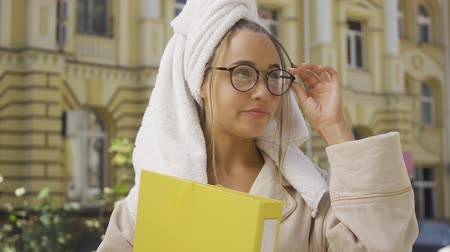 olvidar : Portrait of young woman in bathrobe with towel on head holding folder with documents standing on the street. The girl forget to change dress after shower. Busy life. Freelance