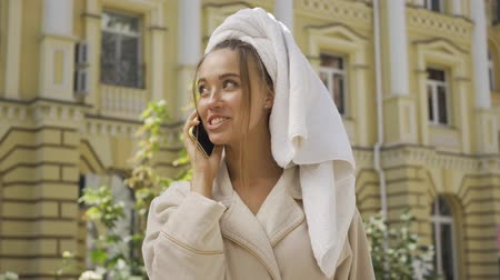 kívül : Portrait of cute smiling jou young woman in bathrobe with towel on head talking by cellphone on the street. Confident girl enjoying a beautiful day in the city