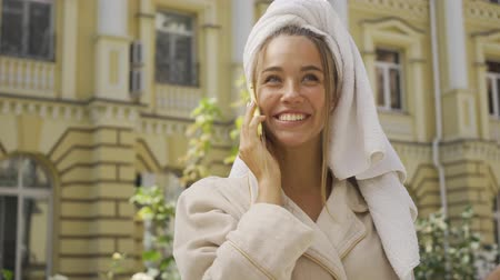 towel white : Portrait of pretty smiling girl in bathrobe with towel on head talking by cellphone on the street. Confident girl enjoying a beautiful day in the city Stock Footage