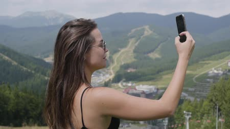 tirol : Pretty young woman taking selfie standing in front of beautiful landscape. Connection with wild nature. Leisure outdoors, active lifestyle. Tourism, traveling Stockvideo
