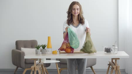 nutrizionista : Young smiling woman putting bags with fruit and vegetables on the table in modern office. Concept of healthy food. Profession of nutri therapist, nutraceutical, nutritionist, wellness coach Filmati Stock