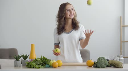 kifejező pozitivitás : Young smiling woman throws up and catches apples standing at the table in modern kitchen. Concept of healthy food. Profession of nutri therapist, nutraceutical, nutritionist, wellness coach Stock mozgókép