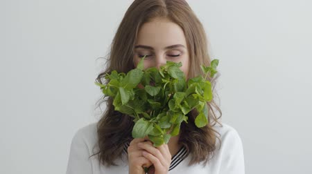 cheirando : Portrait young pretty woman sniffing fresh greens standing at the table in modern kitchen. Concept of healthy food. Profession of nutri therapist, nutraceutical, nutritionist, wellness coach