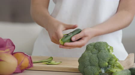 peeler : Close-up of hands of young slim woman peeling cucumber with the sharp knife at the table in the kitchen. Concept of healthy food. Fruit and vegetables lying in the foreground