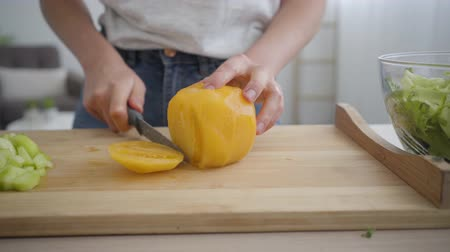 peeler : Close-up of young woman slicing big yellow tomato with the sharp knife at the table in the kitchen. Concept of healthy food. Profession of nutri therapist, nutraceutical, nutritionist
