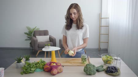 táplálék : Beautiful young slim woman peeling apple with the sharp knife standing at the table in the kitchen. Concept of healthy food. Profession of nutri therapist, nutraceutical, nutritionist
