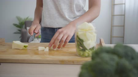 peeler : Close-up hands of young woman slicing big apple with the sharp knife and putting it in the bowl in the kitchen. Concept of healthy food. Profession of nutri therapist, nutraceutical, nutritionist Stock Footage