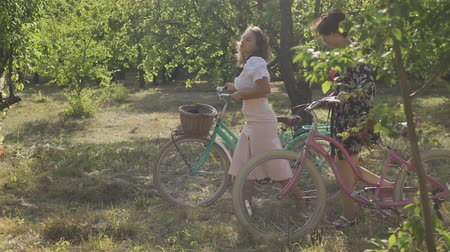 ciclo di vita : Two caucasian young women walking outdoors. Girls talking while leading their bicycles on the narrow road on the street. Rural life. Retro style. Beautiful summer day.