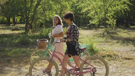 байкер : Two adorable caucasian young girl walking outdoors. Woman talking while leading their bicycles on the narrow road on the street. Rural life. Retro style. Beautiful summer day.