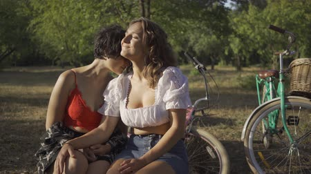 lesbian couple : Two attractive women sitting together in the summer garden, their bicycles standing near. Beautiful lesbian couple. Rural life. Retro style. Hot summer day