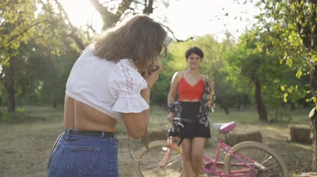 levenscyclus : Attractive young caucasian woman with short hair posing with her bicycle while her friend taking a photo in the garden or park. Rural life. Retro style