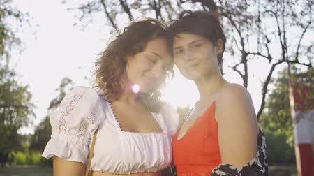 lesbian couple : Portrait of two attractive women looking at camera smiling in front of sun rays. Beautiful lesbian couple enjoying sunset. Romantic date, love, tender relationship