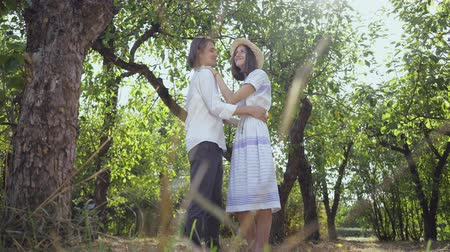 時代遅れの : Happy young man and woman hugging and dancing while standing in the park or garden. Leisure outdoors, connecting with nature, enjoying sunny day. Bottom view 動画素材
